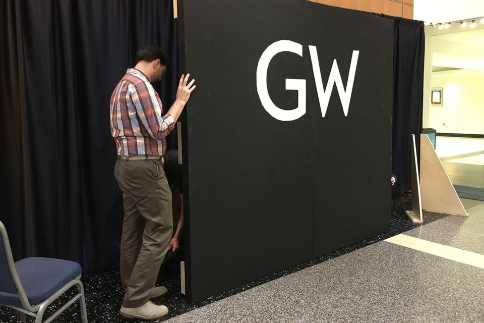 GW Marketing and Creative Services staff assemble the blank wall
